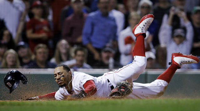 Boston Red Sox's Mookie Betts scores on a double by Andrew Benintendi during the eighth inning of a baseball game against the Toronto Blue Jays at Fenway Park in Boston, Tuesday, Sept. 11, 2018. (AP Photo/Charles Krupa)