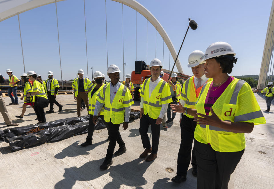 District of Columbia Mayor Muriel Bowser, from right, Secretary of Labor Marty Walsh, and Secretary of Transportation Pete Buttigieg, visit the Frederick Douglass Memorial Bridge construction site in southeast Washington, Wednesday, May 19, 2021. (AP Photo/Manuel Balce Ceneta)