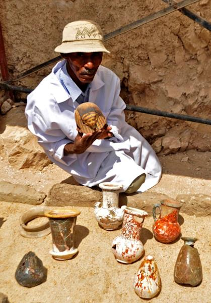 A member of an Egyptian archaeological team shows artifacts discovered in a 3,500-year-old tomb in the Draa Abul Nagaa necropolis, near the southern city of Luxor, on April 18, 2017