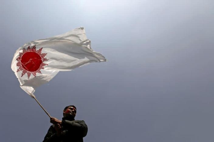 A supporter of a faction of the ruling Nepal Communist Party holds a party flag as he takes part in a rally celebrating the reinstatement of the parliament by Nepal's top court in Kathmandu
