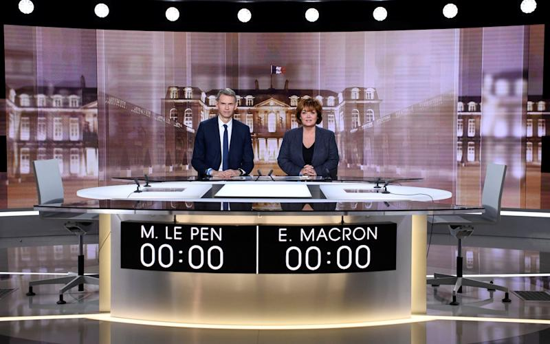 French journalists Christophe Jakubyszyn and Nathalie Saint-Cricq pose on the TV set installed in a studio, ahead of a face-to-face TV debate between the candidates in the 2017 French presidential election - Credit: Reuters