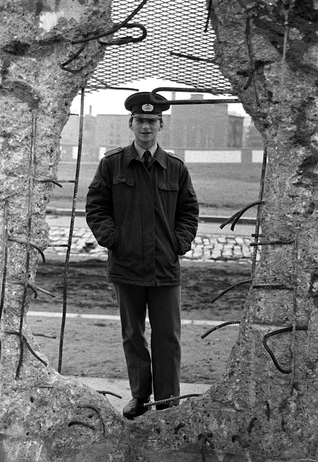 An East German border soldier looks through a large hole in the Berlin Wall on Feb. 8, 1990. (Photo: Fabrizio Bensch/Reuters)