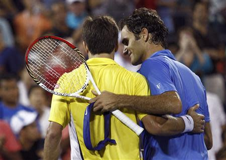 Roger Federer of Switzerland (R) and Tommy Robredo of Spain embrace at the net after Robredo defeated Federer in three sets at the U.S. Open tennis championships in New York September 2, 2013. REUTERS/Eduardo Munoz