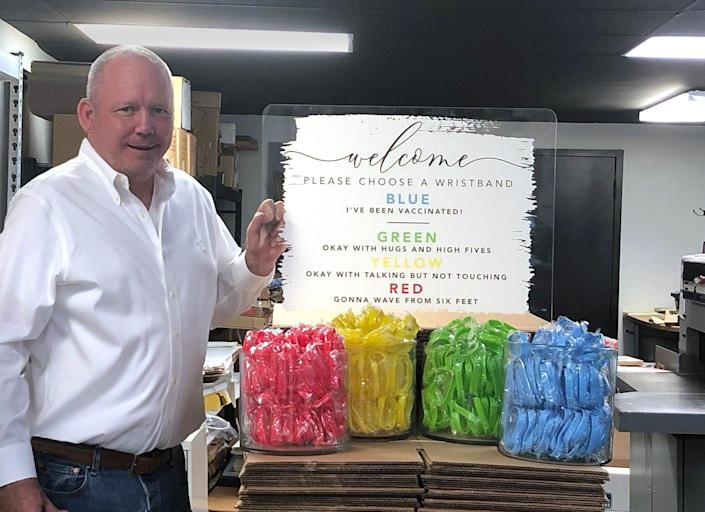 Ron Pollvogt, co-owner of The Elation Factory Co., in Houston, stands near his company's social distancing event kit, which provides attendees with a series of rubber band choices and signage that explains what each color means.