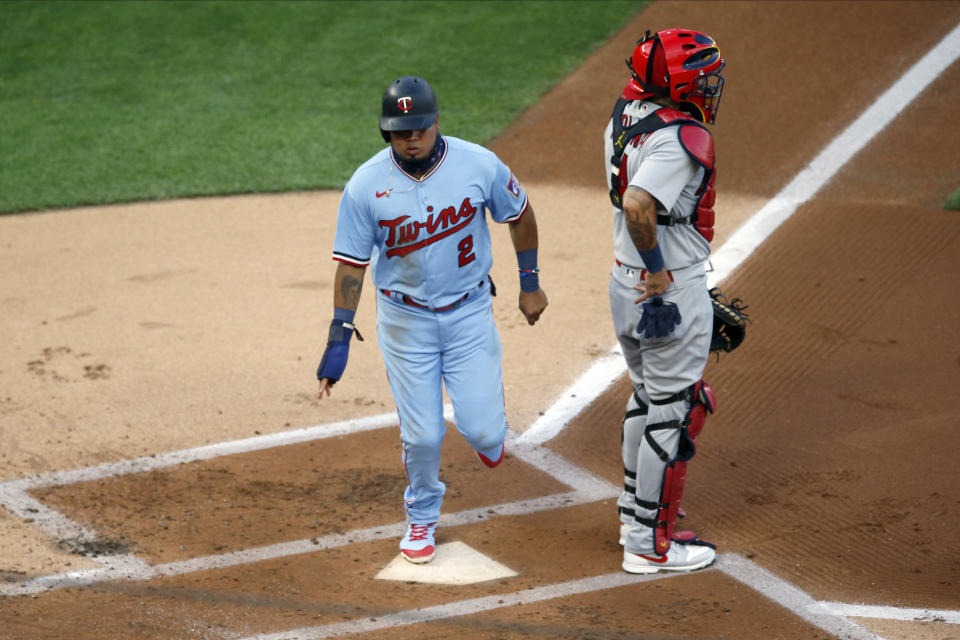 Minnesota Twins' Luis Arraez, left, scores on a two-run double by Nelson Cruz off St. Louis Cardinals pitcher Daniel Ponce de Leon in the xxx inning of a baseball game Wednesday, July 29, 2020, in Minneapolis. (AP Photo/Jim Mone)