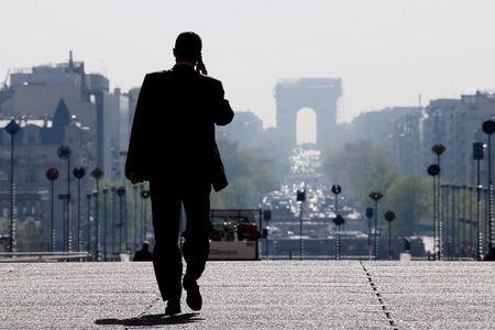 A businessman walks on the esplanade of La Defense, in the financial and business district west of Paris