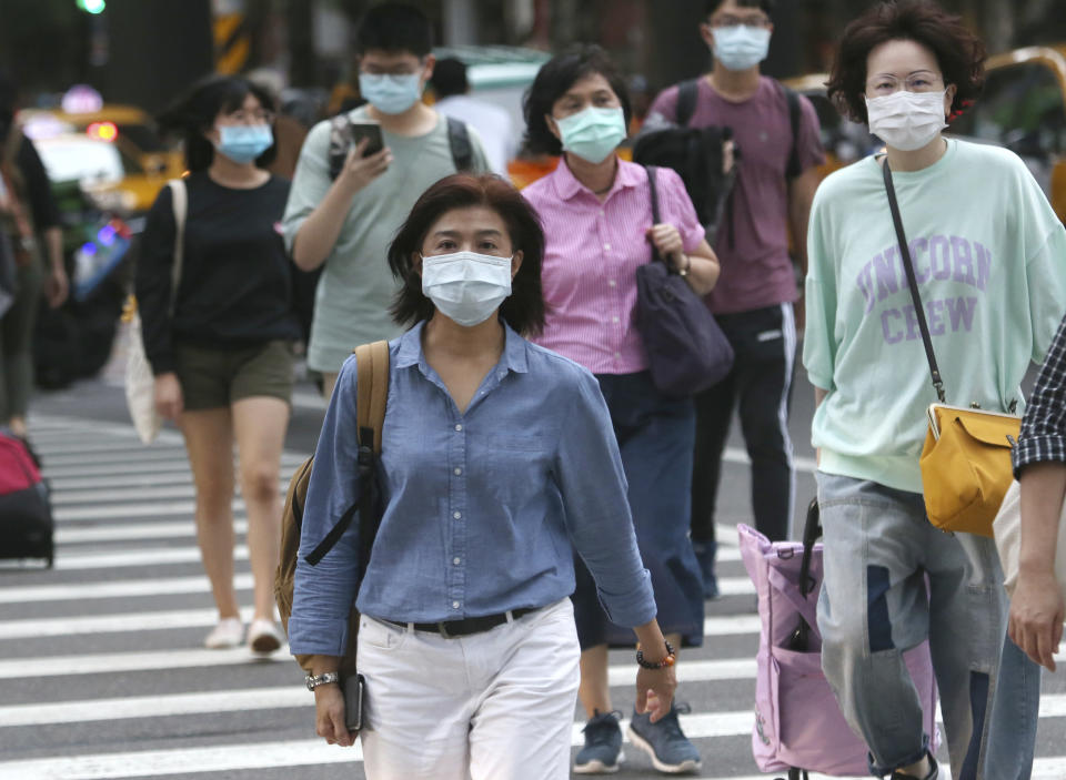 People wearing face masks to protect against the spread of the coronavirus cross and intersection in Taipei, Taiwan, Friday, Nov. 20, 2020. (AP Photo/Chiang Ying-ying)
