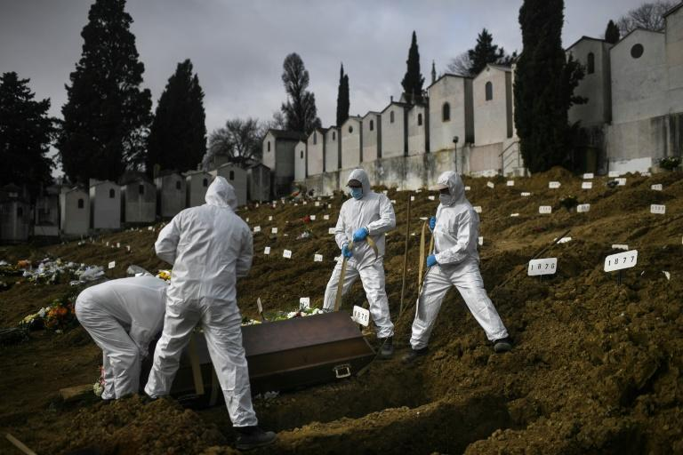 Gravediggers wear protective clothing when they lay suspected Covid-19 victims to rest