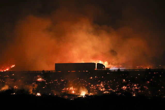 A truck drives along the 101 Freeway as a wildfire continues to burn Tuesday, Dec. 5, 2017, in Ventura, Calif. Raked by ferocious Santa Ana winds, explosive wildfires northwest of Los Angeles and in the city's foothills burned a psychiatric hospital and scores of homes and other structures Tuesday and forced the evacuation of tens of thousands of people. (AP Photo/Jae C. Hong)