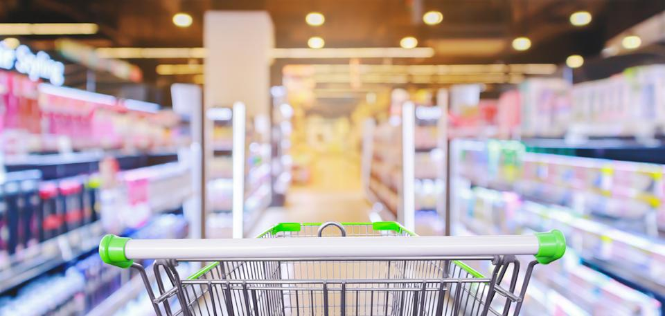 Empty shopping cart with supermarket aisle with cosmetic healthcare product shelves interior defocused blur background