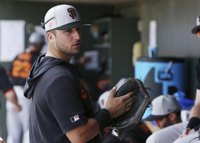 FILE - In this March 6, 2019, file photo, San Francisco Giants' Joey Bart talks with teammates in the dugout prior to the team's spring training baseball game game against the Texas Rangers in Surprise, Ariz. Bart has already made quite an impression in his first big league spring training. The second overall pick in last year's draft, he got to catch Bumgarner's first spring bullpen session last month. (AP Photo/Ross D. Franklin, File)