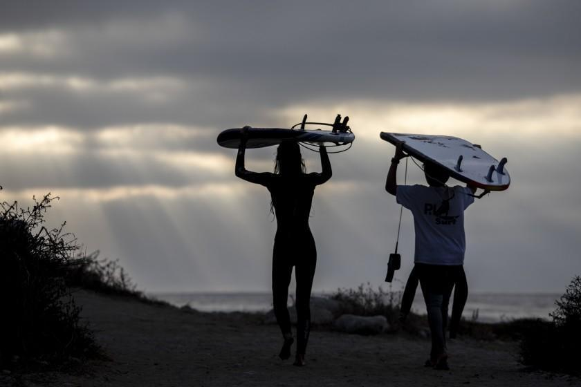 PALOS VERDES ESTATES, CA - OCTOBER 19: Young surfers carry their boards on their heads as they leave Rat Beach, in Palos Verdes Estates, CA, Monday, Oct. 19, 2020. (Jay L. Clendenin / Los Angeles Times)