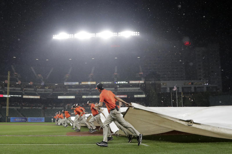 Grounds crew members roll a tarp over the infield during a rain delay during the fifth inning of a baseball game between the Baltimore Orioles and the Tampa Bay Rays, Thursday, Aug. 22, 2019, in Baltimore. (AP Photo/Julio Cortez)