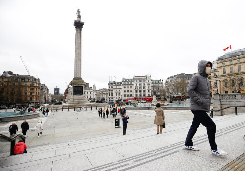 A man wearing a protective face mask walks through Trafalgar Square, as the number of coronavirus cases grow around around the world, in London