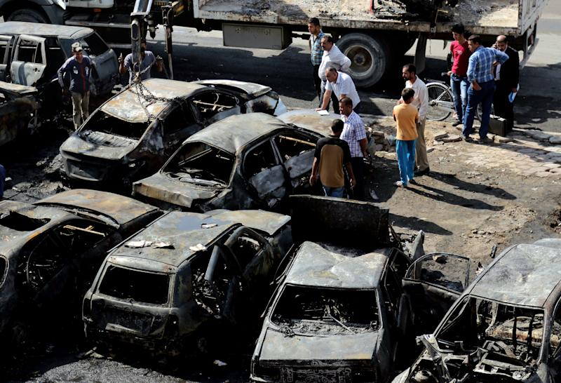 Citizens inspect the site of a car bomb attack in the Sha'ab neighborhood of Baghdad, Iraq, Sunday, Oct. 27, 2013. Insurgents on Sunday unleashed a new wave of car bombs in Shiite neighborhoods of Baghdad, killing and wounding dozens of people, officials said. (AP Photo/ Karim Kadim)