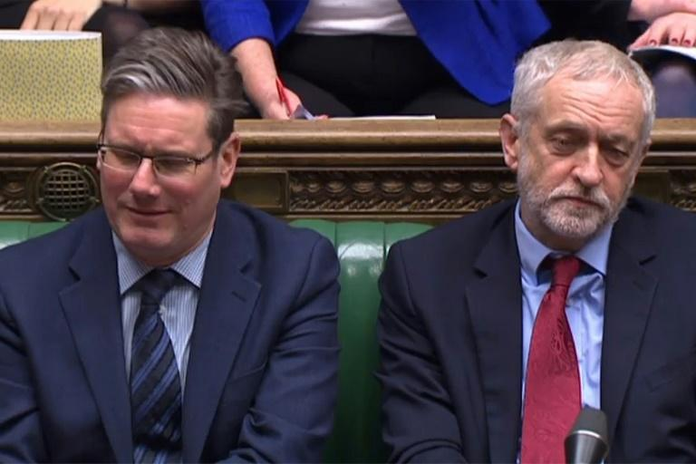 An unimpressed Jeremy Corbyn, Britain's opposition Labour Party leader (r), and his Brexit spokesman Keir Starmer listen on as PM May addresses the House of Commons on Monday