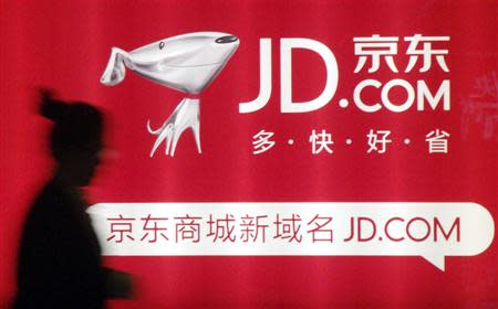 File photo of a woman walking past a advertisement board of Jingdong Mall in Nanjing