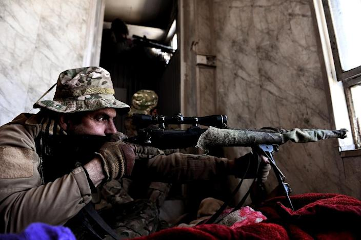 An Iraqi sniper aims his weapon towards Islamic State (IS) fighters during clashes in west Mosul, on March 7, 2017 (AFP Photo/ARIS MESSINIS)