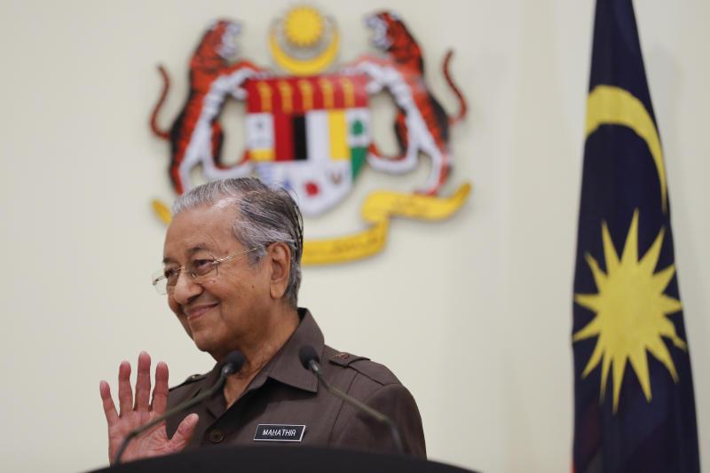 FILE - In this April 15, 2019, file photo, Malaysian Prime Minister Mahathir Mohamad waves good bye to media after a press conference in Putrajaya, Malaysia. Former Prime Minister Mahathir has been ousted from his Malay party in the latest twist to a power struggle with his successor Muhyiddin Yassin, but he has vowed to challenge the move. The 94-year-old Mahathir, along with his son and three other senior members, were expelled from the Bersatu party on Thursday, May 28, 2020. (AP Photo/Vincent Thian, File)