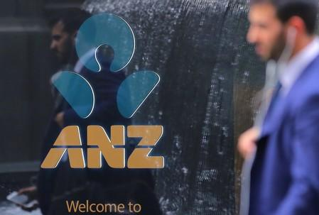 A pedestrian is reflected in the window of a branch of the Australia and New Zealand Banking Group (ANZ) in central Sydney