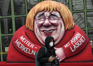 A political carnival float depicting German chancellor Angela Merkel and her possible successor Governor Armin Laschet is rolled out to be shown in the streets of Duesseldorf, Germany, Monday, Feb. 15, 2021. Because of the coronavirus pandemic the traditional 'Rosenmontag' carnival parade are canceled but eight floats are pulled through the empty streets in Duesseldorf, where normally hundreds of thousands of people would celebrate the street carnival. (AP Photo/Martin Meissner)