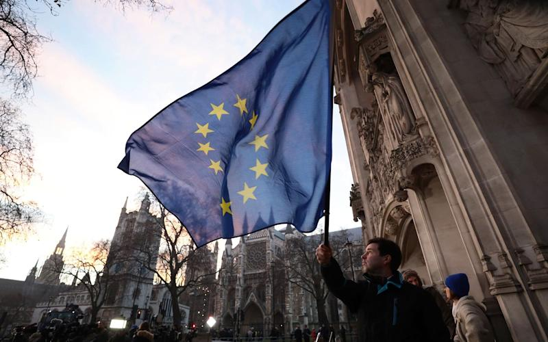 A demonstrator waves a European Union flag outside the Supreme Court  - Credit: Simon Dawson/Bloomberg