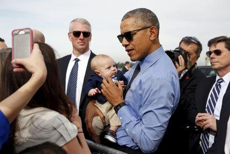 U.S. President Barack Obama poses with a baby before boarding Air Force One as he departs from Moffett Field in Mountain View, California