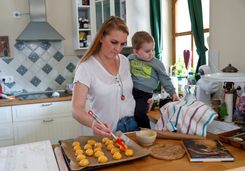 Eszter Harmath holds her son Gellert, as she prepares pastries at her home, during COVID-19 pandemic in Szentendre