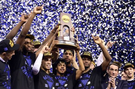 Duke Blue Devils guard Quinn Cook (middle) and teammates hoist the NCAA championship trophy after defeating the Wisconsin Badgers in the 2015 NCAA Men's Division I Championship game at Lucas Oil Stadium. Mandatory Credit: Bob Donnan-USA TODAY Sports