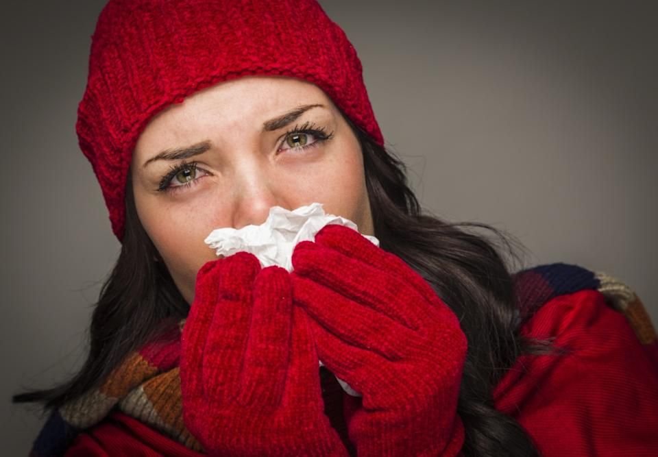 Woman Wearing Winter Hat and Gloves Blowing Her Sore Nose with a Tissue