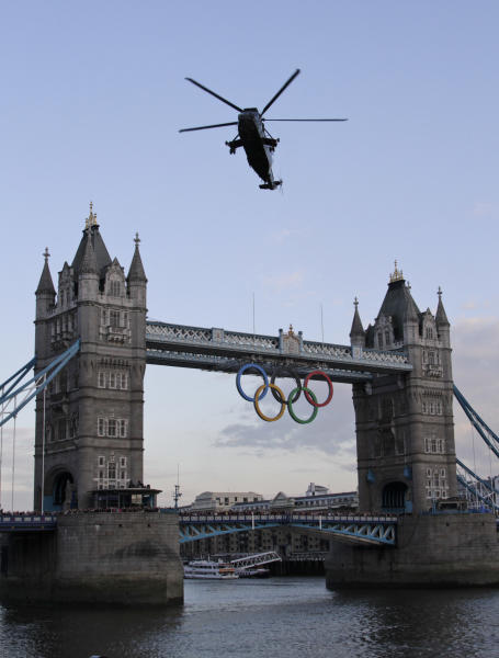 A British Royal Marine Sea King helicopter carrying the Olympic flame flies past the Tower Bridge in London, as it arrives to the Tower of London, Friday, July 20, 2012. The Olympic Torch arrived in London after it was carried around England in a relay of torchbearers to make its way to the London 2012 Olympic Games opening ceremony on July 27, 2012. (AP Photo/Lefteris Pitarakis)