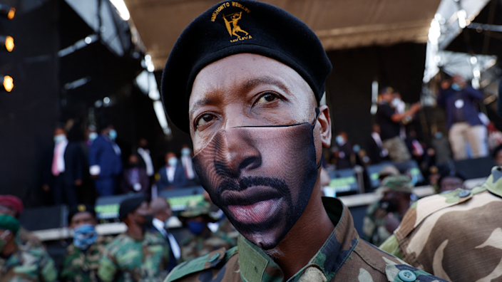 A member of the uMkhonto we Sizwe Military Veterans Association (MKMVA), in a face mask, stands next to a stage moments before former South African President Jacob Zuma addresses his supporters in Pietermaritzburg, South Africa - Wednesday 26 May 2021