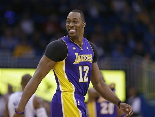 Los Angeles Lakers' Dwight Howard (12) smiles as walks on the court after a time out late in the fourth quarter during an NBA basketball game against the Orlando Magic, Tuesday, March 12, 2013, in Orlando, Fla. Los Angeles won the game 106-97.(AP Photo/John Raoux)
