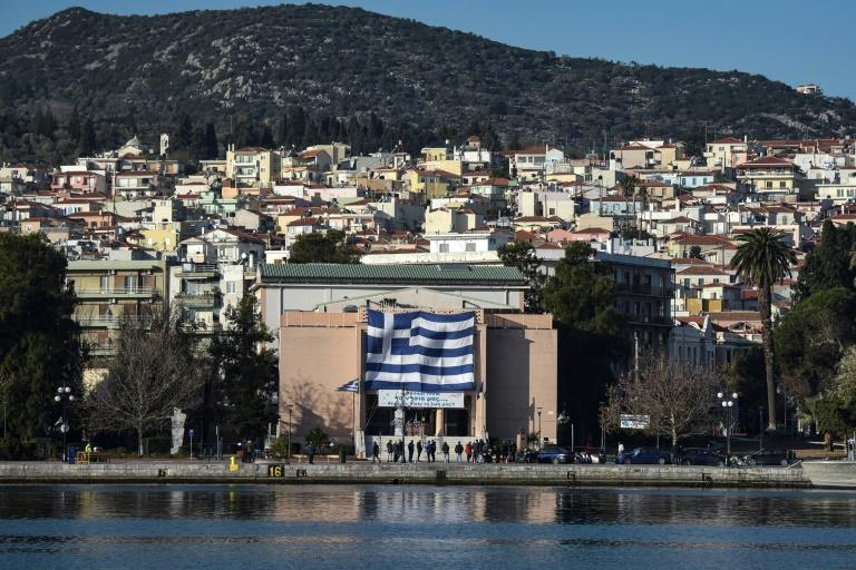 """A big Greek flag hung on the facade of the municipal theatre of Mytilene on Lesbos along with a banner reading """"We want our islands back, we want our lives back"""""""