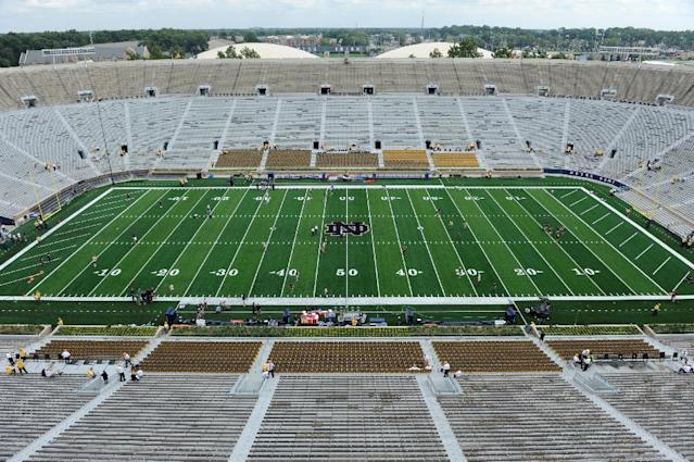 Players loosen up on the new artificial field before an NCAA college football game between Notre Dame and Rice in South Bend, Ind. Saturday Aug. 30, 2014. (AP Photo/Joe Raymond)
