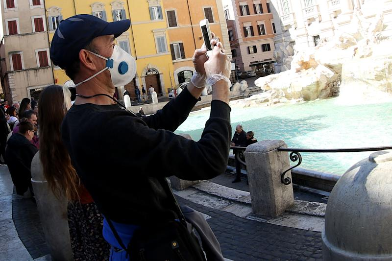 ROME, ITALY - MARCH 11: A tourist wearing a protective mask and gloves takes a picture at the Trevi Fountain on March 11, 2020 in Rome, Italy. The Italian Government has taken the unprecedented measure of a nationwide lockdown in an effort to fight the world's second-most deadly coronavirus outbreak outside of China. The movements in and out are allowed only for work and health reasons proven by a medical certificate. The justifications for the movements needs to be certified with a self-declaration by filling in forms provided by the police forces in charge of the checks. (Photo by Franco Origlia/Getty Images)