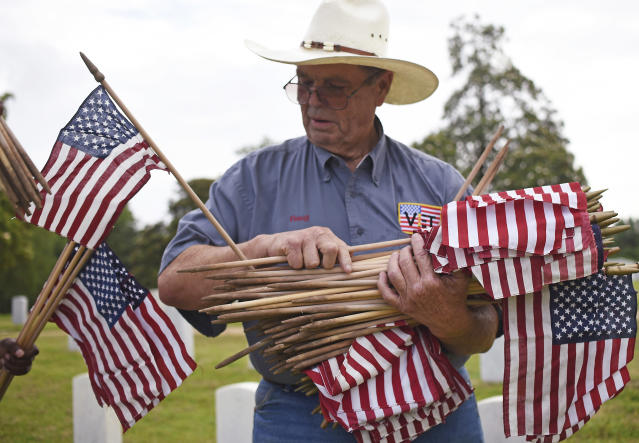 <p>Doug McCallister passes out U.S. flags Saturday, May 26, 2018 for volunteers to place in front of the tombstones at the Natchez National Cemetery in Natchez, Miss., as the community honors those who died in service to their country. (Photo: Nicole Hester/The Natchez Democrat via AP) </p>