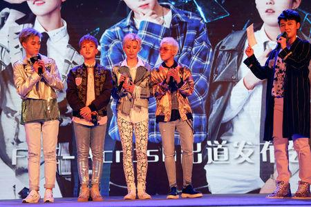"Members of China's all-girl ""boyband"" FFC-Acrush appear on the stage during their maiden press conference in Beijing"