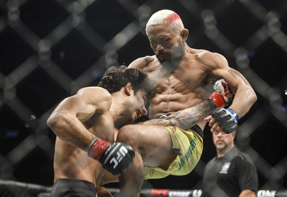 FILE - In this July 27, 2019, file photo, Deiveson Figueiredo, right, knees Alexandre Pantoja during a mixed martial arts bout at UFC 240 in Edmonton, Alberta. The UFC is hoping to stoke interest in its men's flyweight division with the main-event matchup of Brazilian champion Deiveson Figueiredo and American contender Alex Perez at UFC 255, Saturday night in Las Vegas. (Jason Franson/The Canadian Press via AP, File)