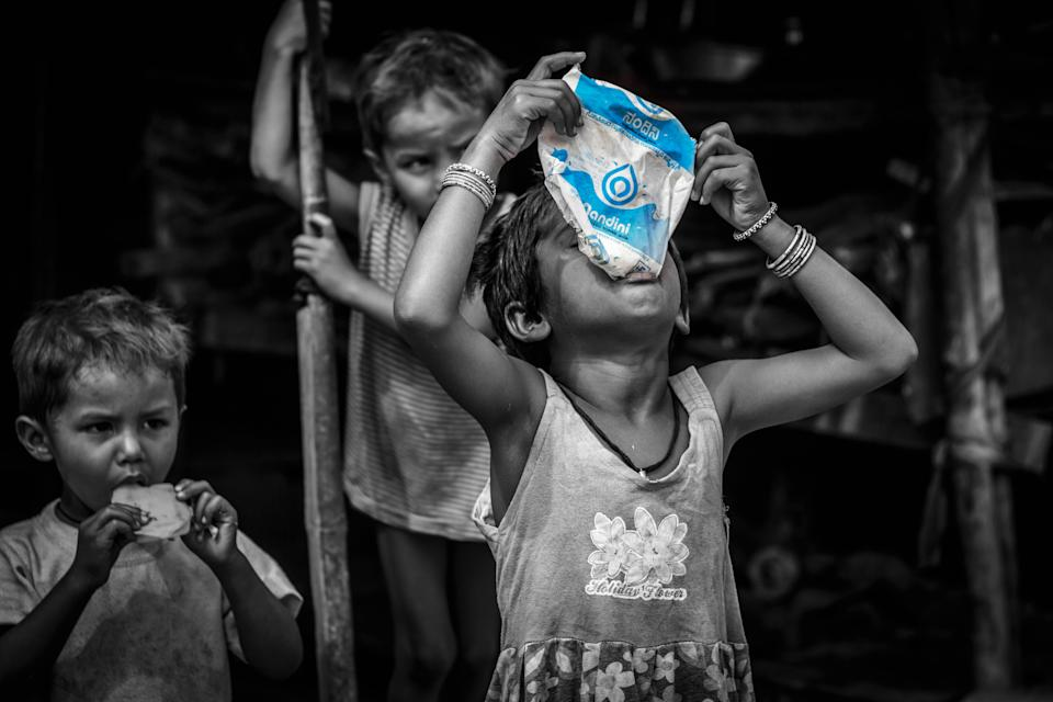 A girl child drinking milk from the milk packet distributed by Mission Milk