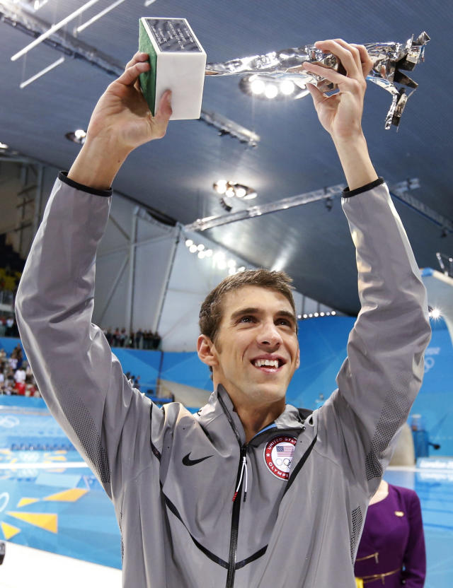 "Michael Phelps of the U.S. holds up his trophy awarded to him by FINA honouring him as the most decorated Olympian of all time, after winning the men's 4x100m medley relay final during the London 2012 Olympic Games at the Aquatics Centre August 4, 2012. Phelps ended his incredible Olympic career on the perfect note on Saturday, winning his 18th gold medal for the United States in the men's medley relay, the last time he will swim a competitive race. The trophy reads, ""To Michael Phelps, the greatest Olympic athlete of all time, from FINA"". REUTERS/Jorge Silva (BRITAIN - Tags: SPORT SWIMMING OLYMPICS)"