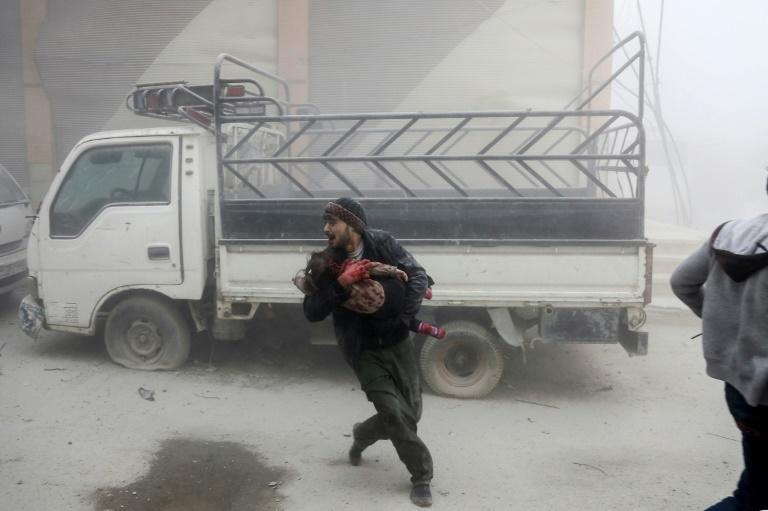 A man carries a child as he flees from reported Syrian air strikes in rebel-held Eastern Ghouta on February 6, 2018