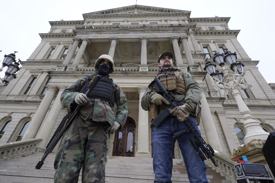 FILE - In this Jan. 6, 2021 file photo, armed men stand on the steps at the State Capitol after a rally in support of President Donald Trump in Lansing, Mich. Statehouses where Trump loyalists have rallied since the Nov. 3 election are heightening security after the storming of the U.S. Capitol this week. Police agencies in a number of states are monitoring threats of violence as legislatures return to session and as the nation prepares for the inauguration of President-elect Joe Biden. (AP Photo/Paul Sancya, File)