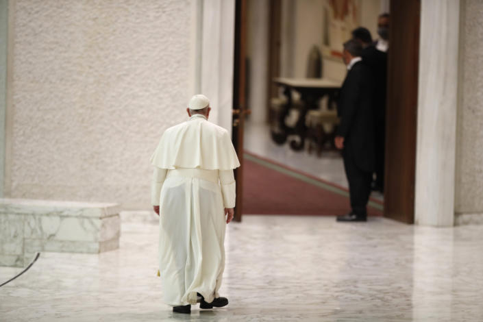 "Pope Francis leaves at the end of his weekly general audience in the Paul VI Hall at the Vatican, Wednesday, Oct. 28, 2020. Pope Francis has blamed ""this lady COVID"" for forcing him to keep his distance from the faithful during his general audience, which was far smaller than usual amid soaring coronavirus infections in Italy. (AP Photo/Alessandra Tarantino)"