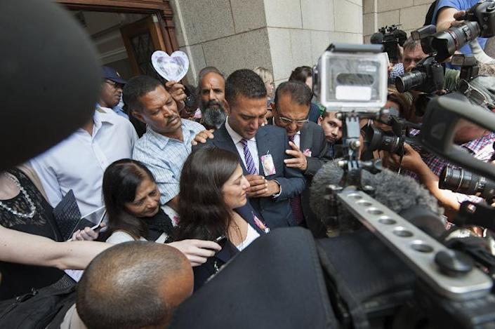 Anish and Vinod Hindocha(centre, left and right) brother and father of murdered tourist, Anni Dewani face the waiting media, after Dewani's husband Shrien Dewani was acquitted of her murder in Cape Town on December 8, 2014 (AFP Photo/Rodger Bosch)