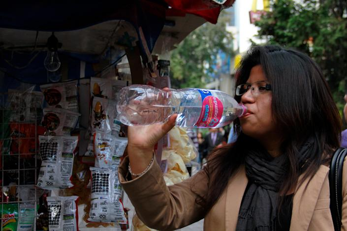 In this Jan. 9, 2014 photo, a woman drinks bottled water in Mexico City. Bad tap water accounts in part for Mexico being the highest consumer of bottled water and sweetened drinks. A law recently approved by Mexico City's legislators will require all restaurants to install filters, offering patrons free, apparently drinkable potable water that won't lead to stomach problems and other ailments. With an obesity epidemic looming nationwide, the city's health department decided to back the water initiative. (AP Photo/Marco Ugarte)