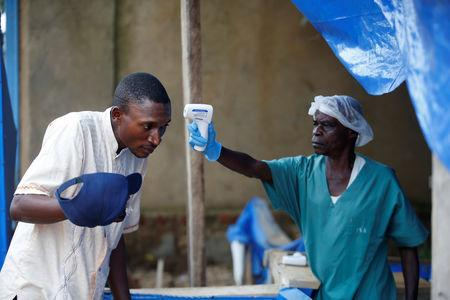 A health worker measures the temperature of a man entering the ALIMA (The Alliance for International Medical Action) Ebola treatment centre in Beni, in the Democratic Republic of Congo, April 1, 2019. Picture taken April 1, 2019. REUTERS/Baz Ratner