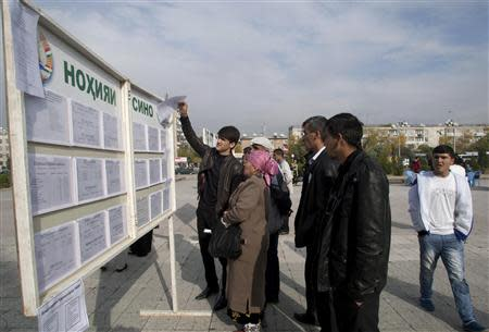 People stand in front of an information board with job vacancies in Dushanbe