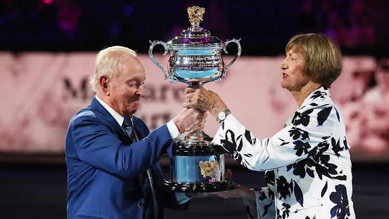 Seen here, Rod Laver hands Margaret Court a replica Australian Open trophy.