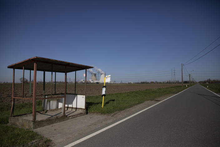 An empty bus stop on a deserted road in Doel, Belgium, Monday, March 23, 2020. Belgium's stores, schools, restaurants and bars have closed and citizens have been asked to stay at home or to maintain a social distance from others. For most people, the new coronavirus causes only mild or moderate symptoms, such as fever and cough. For some, especially older adults and people with existing health problems, it can cause more severe illness, including pneumonia. (AP Photo/Virginia Mayo)